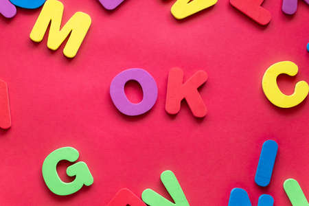 Word OK From Plastic Magnetic Letters On Red Background.