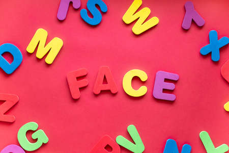 Word FACE From Plastic Magnetic Letters On Red Background.