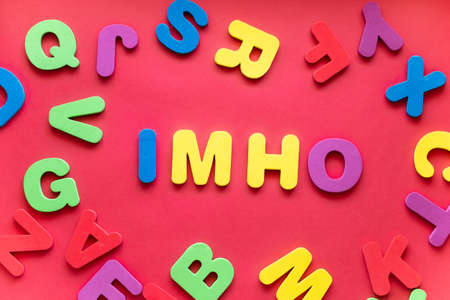 Abbreviation IMHO From Plastic Magnetic Letters On Red Background.