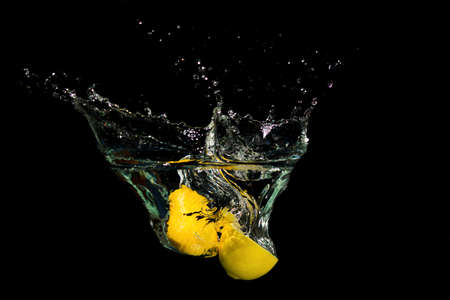Fresh lemon drop in the water on black background Reklamní fotografie