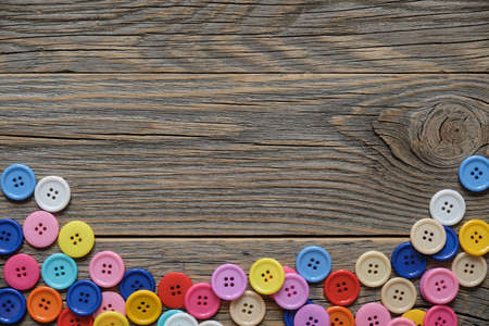 Colorful sewing buttons creating a frame on a wooden background with space for text. Фото со стока