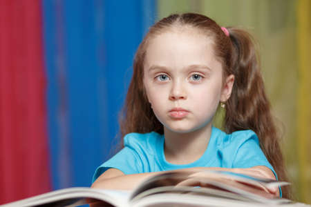 education and school concept - little girl with an open book