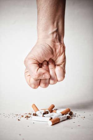 Man's hand crushing cigarettes. now stop smoking