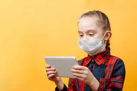 A Teenage Girl In A Medical Mask On A Yellow Background Is Holding A Tablet PC.