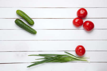 colorfully: Vegetable composition - tomato, cucumber and green onion on white wooden background. top view