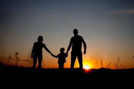 comprising: Silhouette of a family comprising a father, mother, and a child. Concept of friendly family.