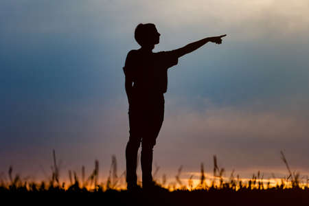 mujer mirando el horizonte: Silhouette of the woman standing lonely at the field during beautiful sunset Foto de archivo