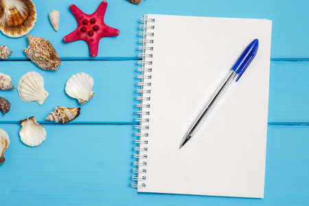navy blue background: Blank notepad and Sea star and shells on wooden blue background.