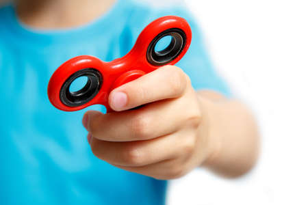 cool gadget: Little girl play with modern finger spinner.Cool fidget spin toy closeup.New spinning device.