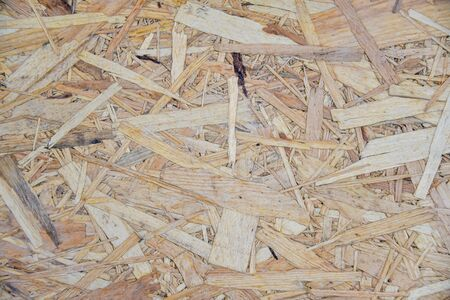 OSB sheet is made of brown wood chips pressed together into a wooden floor