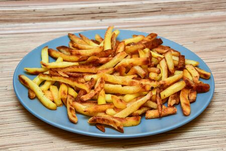 french fries on a blue plate on a wooden background.