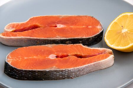 Close up fresh raw salmon red fish steak with lemon slice on a plate.