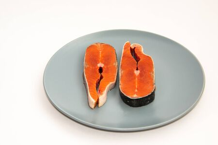 Two fresh raw salmon red fish steaks on a plate, isolated on white background.