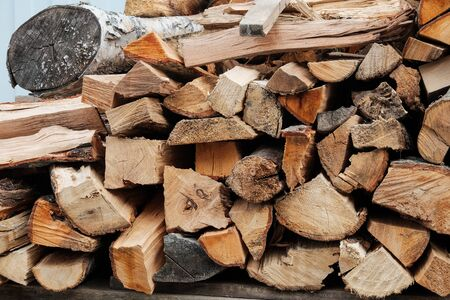 Preparation of firewood for the winter. Stacks of firewood. Pile of firewood.