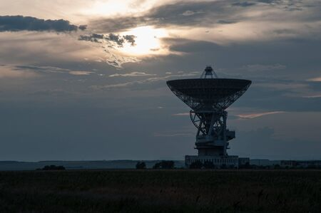 Space radar antenna. Satellite dish at sunset with cloudy sky.