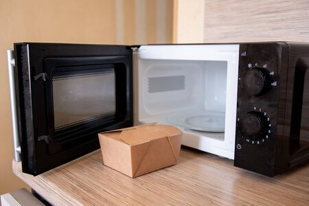 Close-up of a food box next to a microwave ready for heating. 免版税图像