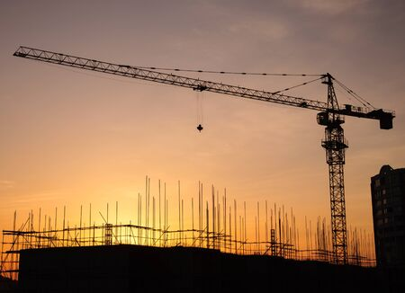 Silhouette of a crane in a construction site at sunset background