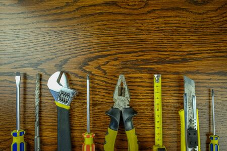 Construction tools laid out on a wooden background. Screwdrivers, wrenches, tape measure, knife, pliers, drill. Copy space. Banque d'images