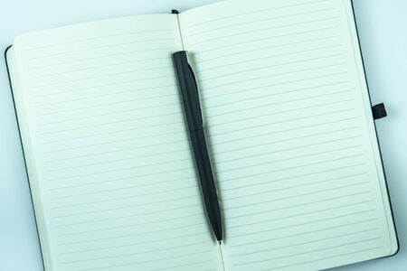 Open white notebook paper and pen on light table background with copy space. Banque d'images