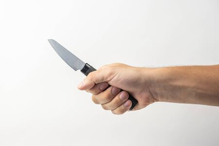 Small kitchen knife in man hand on white background. isolated on white background. Man threaten somebody with knife. Killer concept. Cooking equipment.