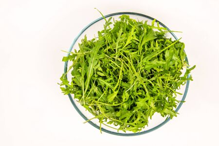 Green arugula leaves in a glass bowl. Top view. Healthy eating concept. Reklamní fotografie