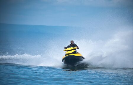 Young man of jet ski rider performs on the waves with much splashes.