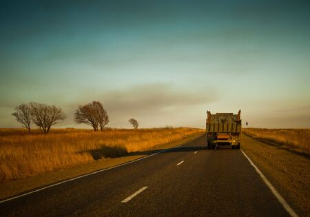 Cars and trucks drive along a beautiful scenic highway among fields on a sunny summer day. Stock fotó