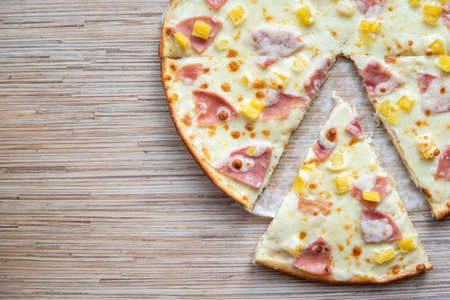 Sliced slice of hawaiian pizza on a wooden background top view with copy space. Stock fotó