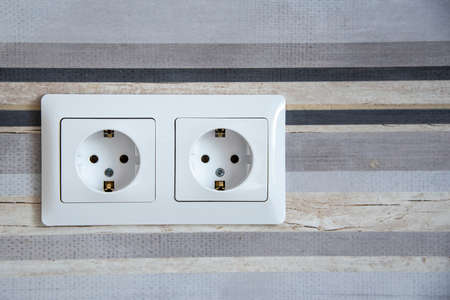 Two white Power sockets with frame on ceramic tile as a background with copy space