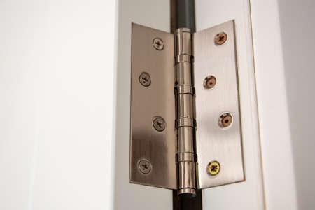 door hinges Aluminum on white door close up.