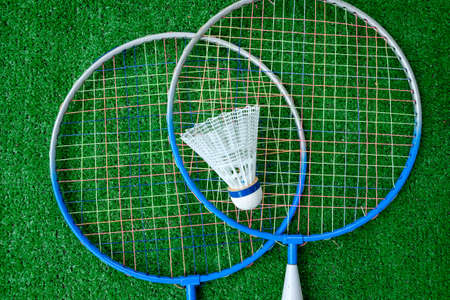 Two badminton mini rackets with white shuttlecock on the green background, active games.