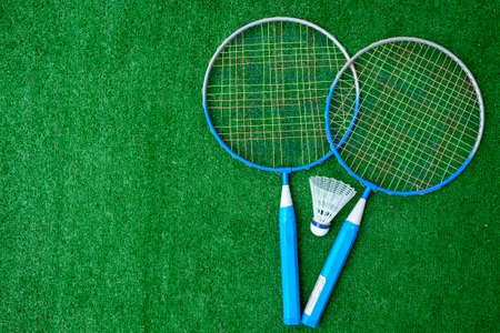 Two badminton mini rackets with white shuttlecock on the green background, active games. copy space.