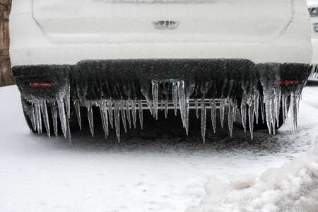 Ice-covered car bumper with icicles close up, vehicle parking safety after freezing rain in Europe.