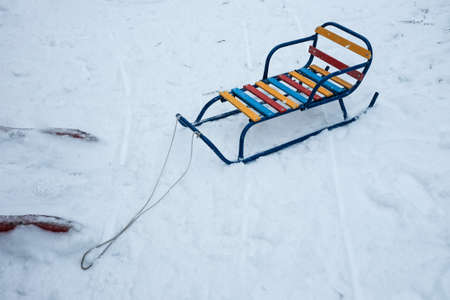 color wood and metal children sledges on the white snow.