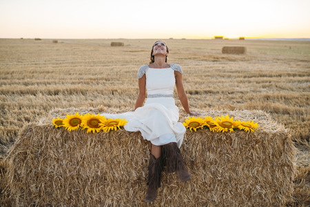 Happy woman in sunflower field and in the field of straw 免版税图像