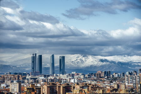 Madrid Skyline from the air, snowy in the background mountains