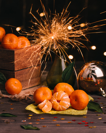 New Years concept. Tangerines in a wooden box. Sparkler burns in a vase. New Years, Christmas decorations. Dark wall with a garland on the background. Vertical orientation
