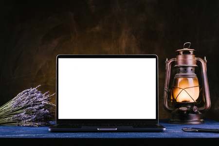 A laptop with a blank screen stands on a blue wooden table next to a kerosene lamp, a bouquet of lavender and a notebook with a pen. Dark textured wall on the background Stock Photo