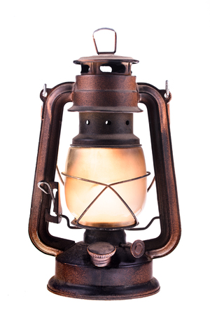 Gas lantern with burning light, isolated on a white background. An antique vintage lamp. Hipster accessory. Camping light. Interior decoration. Oil lamp. Kerosene lantern. Rusty, covered with patina. Metal case, smoked frosted glass.