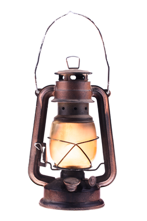 Gas lantern with burning light, isolated on a white background. An antique vintage lamp. Hipster accessory. Camping light. Interior decoration. Oil lamp. Kerosene lantern. Rusty, covered with patina. Metal case, smoked frosted glass. Wire handle up
