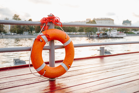 Orange lifebuoy on the river dock. Safety on the water. The river and the buildings on the background.