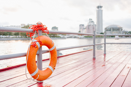 Orange lifebuoy on the river dock. Safety on the water. The river cruise ship and the Moscow International Performing Arts Center on the background.