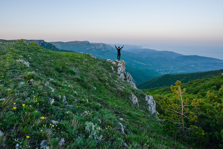 A pleasant evening mountain landscape. The figure of a man with his hands up in the center of the frame. Alpine meadow with flowers in the foreground