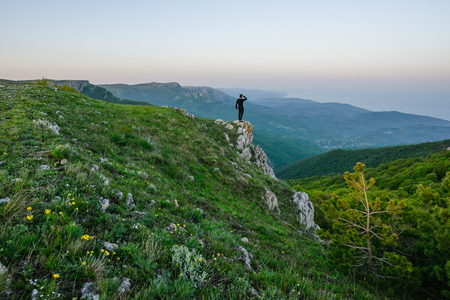 A pleasant evening mountain landscape. The figure of a man staring into the distance in the center of the frame. Alpine meadow with flowers in the foreground