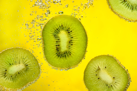 Sliced pieces of kiwi covered with bubbles falling in water on yellow background.