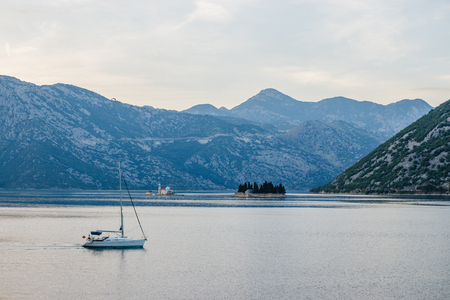 Mediterranean, Adriatic vacation. Yacht in the bay. Evening light. Mountains on background. Our Lady of the Rocks and St. George islands. Montenegro, Kotor Bay