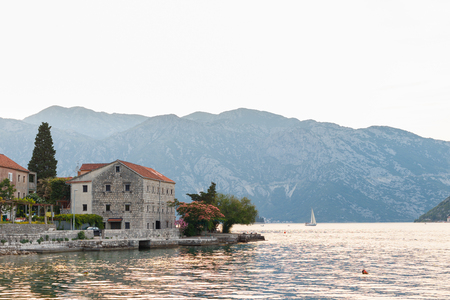 Picturesque bay. Old Mediterranean, Adriatic buildings on the shore. Yacht in the bay. Evening light. Free space for text on the right. Stock Photo