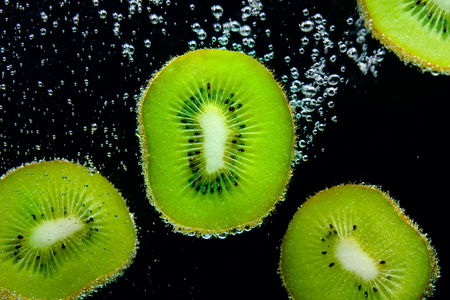 Sliced pieces of kiwi covered with bubbles falling in water on black background.  Stock Photo