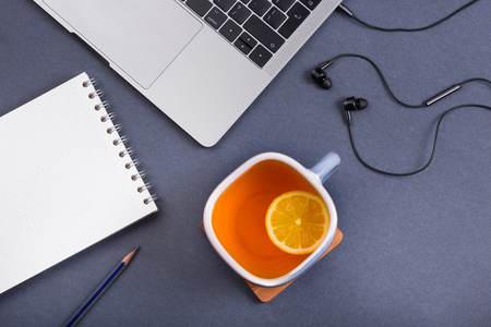 Tea with lemon, laptop, headphones, pencil and notebook on a gray background. View from above, flatlay, flat-lay. Tea drinking at work in the office.  Stock Photo