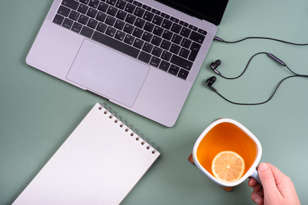 Tea with lemon, laptop, headphones, emty notebook on a mint green background. View from above, flatlay. Tea drinking at work. Hand holds a cup